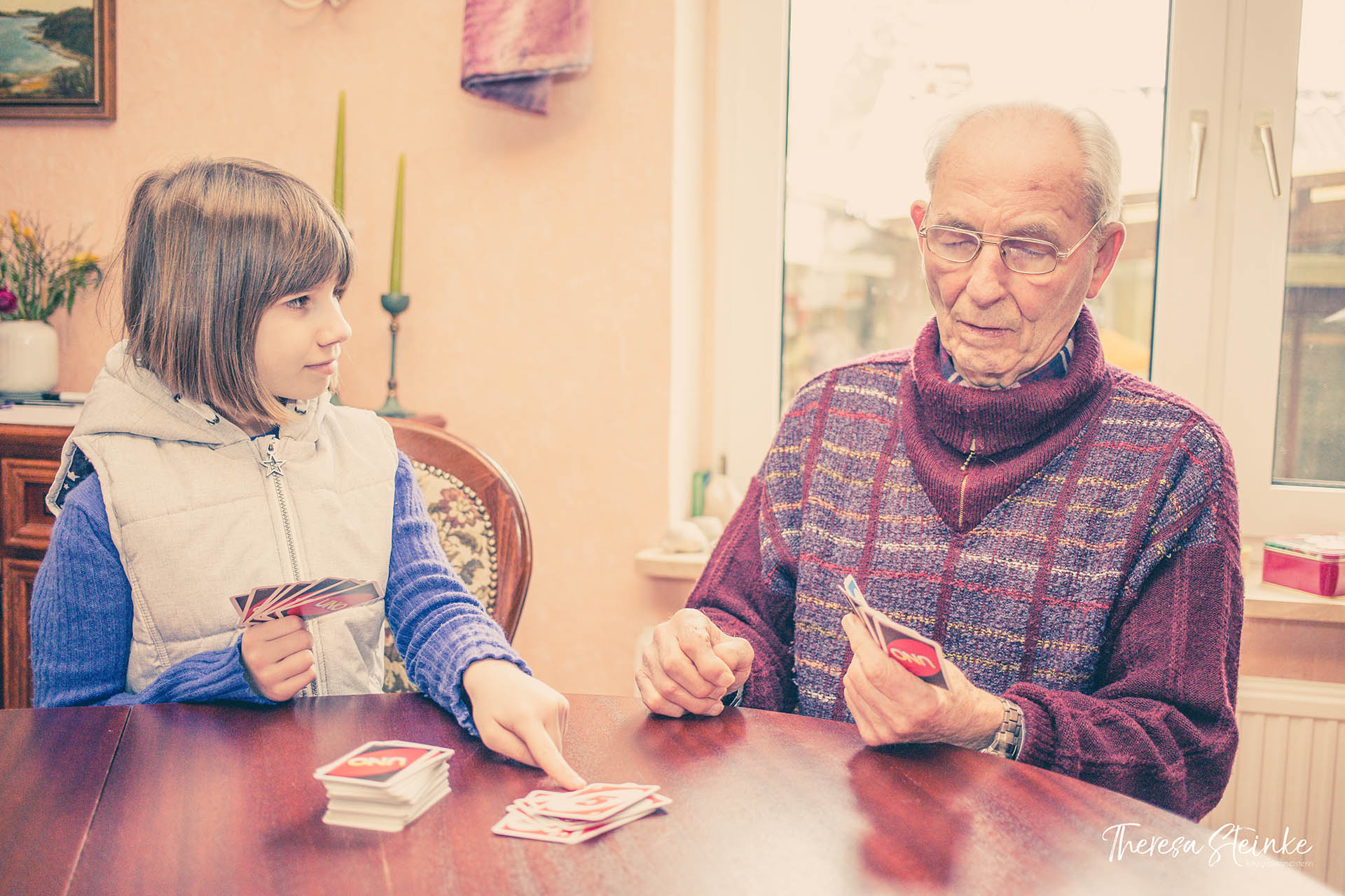Älterer Mann spielt mit Mädchen Karten