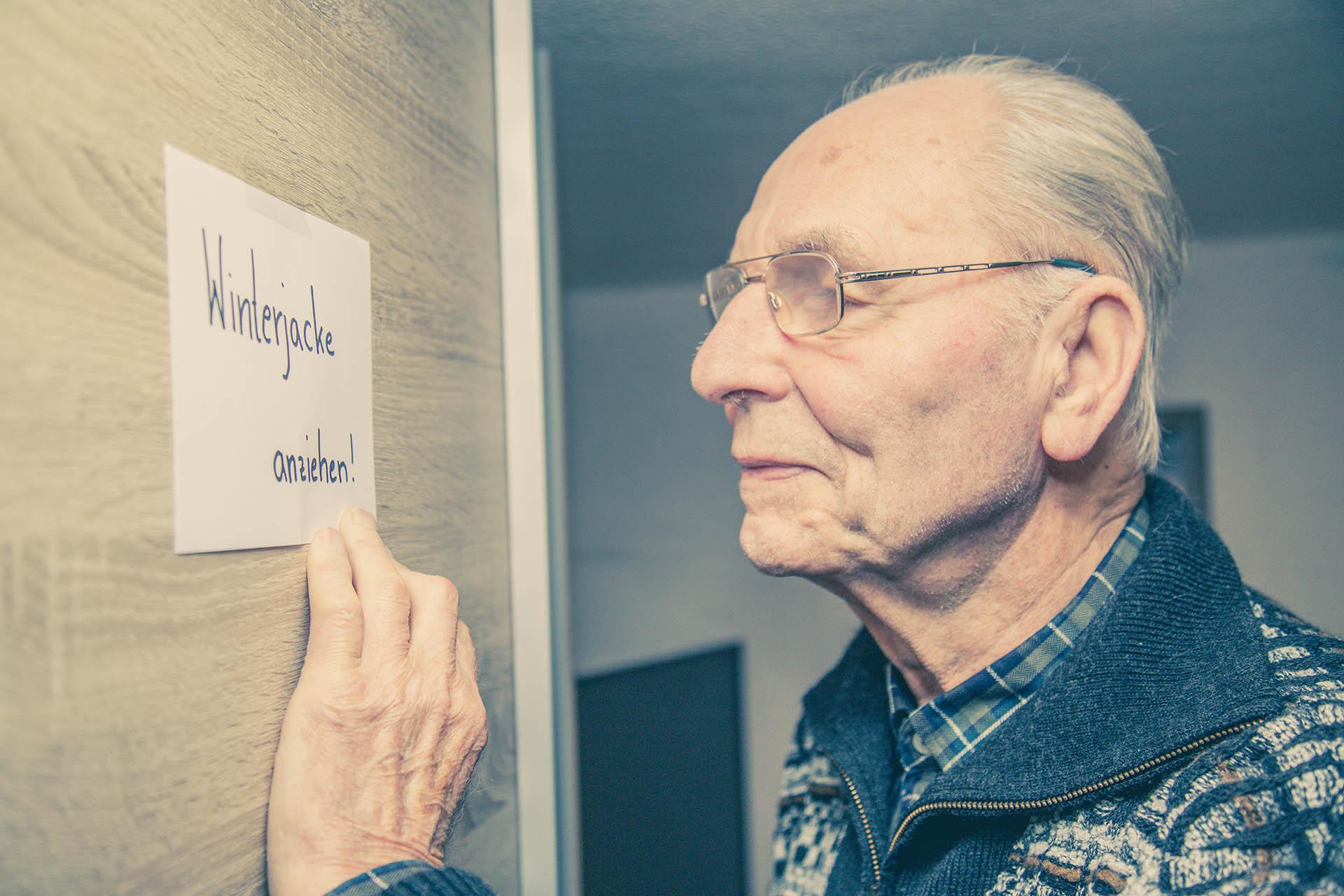Älterer Mann liest einen Zettel