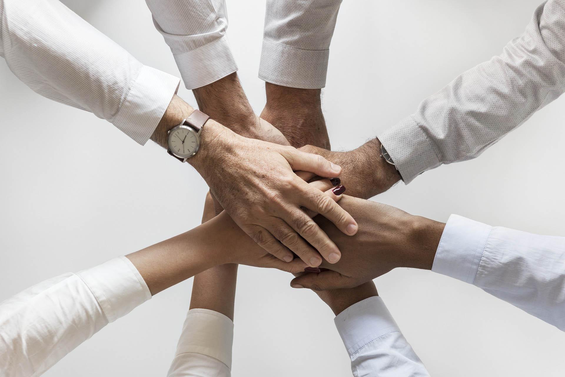 Hände übereinander als Team